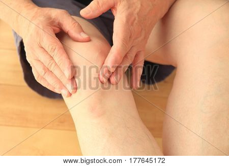 An older man indicates where his knee is hurting