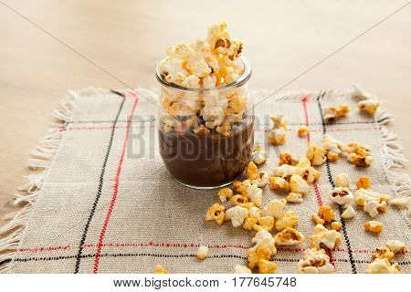 Chocolate dessert with popcorn on wooden table. Homemade cacao tasty pudding.