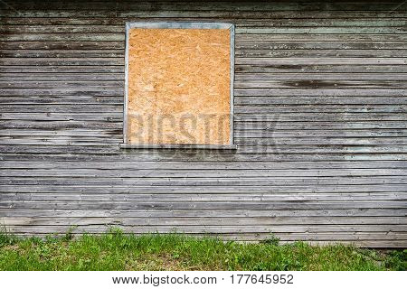 Weathered wooden plank house wall with boarded up window