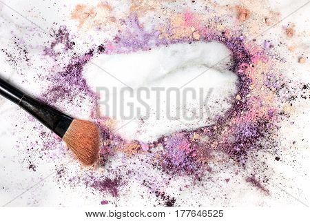 Makeup brush on white marble background, with traces of powder and blush forming a frame. A horizontal template for a makeup artist's business card or flyer design, with copy space