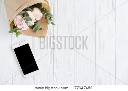 Simple feminine background with smartphote mock-up and roses on white wooden tabletop, elegant lady blogger workspace