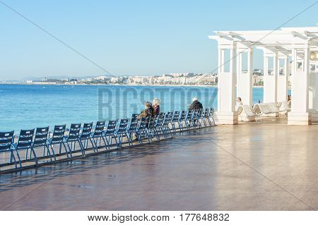 Nice, France - 25 February, People rest on the waterfront of Nice, 25 February, 2017. People and tourists having a rest on the Cote d'Azur.