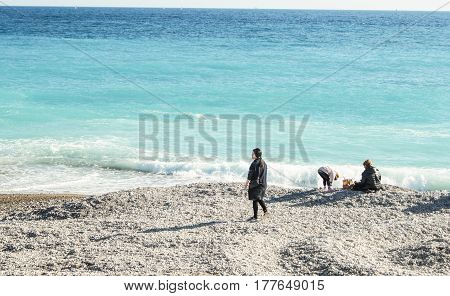 Nice, France - 25 February, People at the water's edge, 25 February, 2017. People and tourists having a rest on the Cote d'Azur.