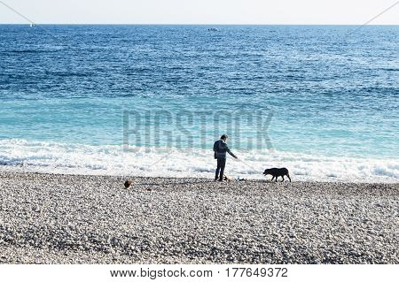 Nice, France - 25 February, The man with the dog on the beach, 25 February, 2017. People and tourists having a rest on the Cote d'Azur.