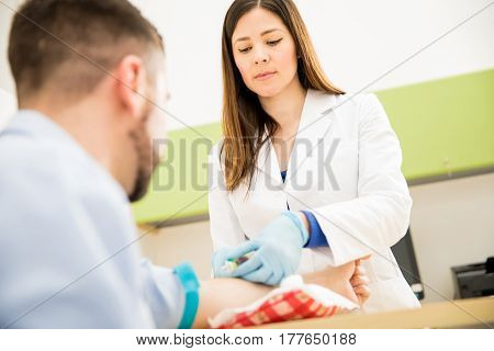 Female Doctor Drawing Blood From Patient