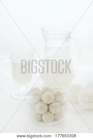White sweets with coconut shavings plate with marshmallows glass jug and glass with milk on a white background.