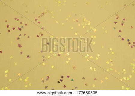 A shiny sparkly golden mini heart confetti background