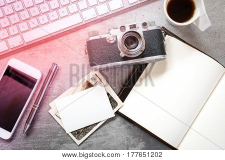 Photographers workspace on a concrete desk with camera, computer, phone, notebook, photos and coffee