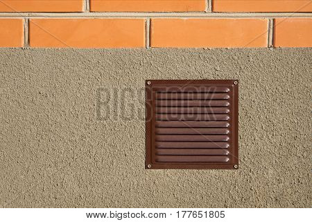 Steel brown ventilation grille in the wall outdoors