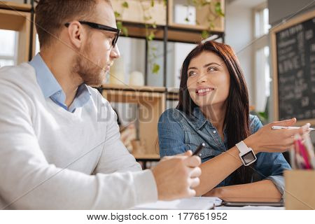 Professional relationships. Positive beautiful friendly woman holding a pen and smiling while looking at her male colleague