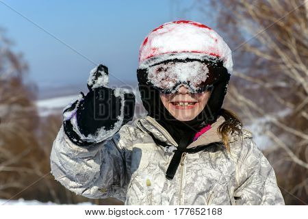 Girl skier, in protective helmet and glasses shows thumb up