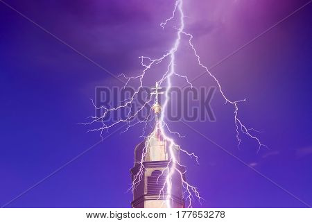 top of church tower with lightning and blue and purple sky
