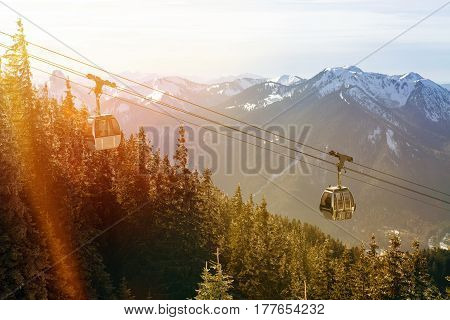 cableway with forest and snowy mountain peaks at sunset