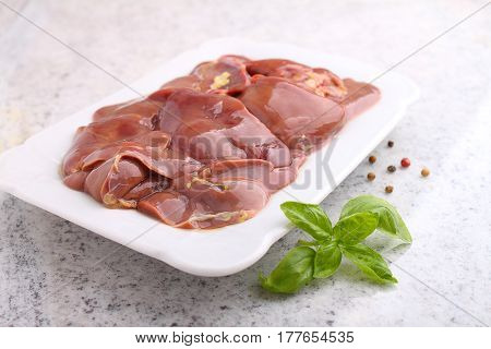 Chicken raw liver in a white plate on a white background