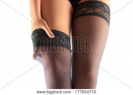 Close up of sexy woman put on her black nylon stockings on long fit legs isolated on white background horizontal view