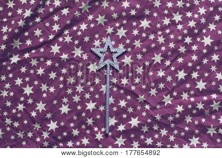 top view of wrinkled background texture of purple textile table cloth with white stars and silver magic wand in the center