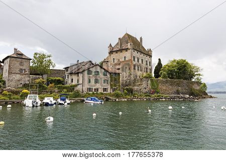 Yvoire France - May 24 2013: Medieval castle that is beautifully situated on the shore of Lake Geneva. Other stone houses in the immediate vicinity complement the impression that time has stopped here.