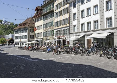 Lucerne Switzerland - May 08 2016: Buildings at the square that is named Muehlenplatz where on the ground floor operates outdoor seating restaurant and there is parking place for bikes. A few people in a distance can be seen.