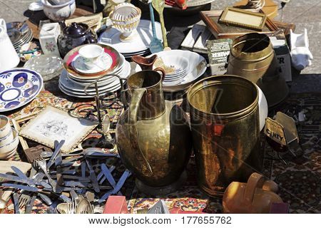 Nice France - May 17 2014: The variety of items for sale during the flea market. On the table are plates copper crockery cutlery and many others that can be seen