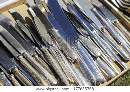 Nice France - May 17 2014: Table knifes in large quantities offered for sale during the flea market which was held on one of the squares in the city. These cutlery shows signs of use such as visible scratches and on a few of them can be seen placed there