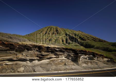 Stock photo of a highway and volcanic mountain in Hawaii with deep blue sky