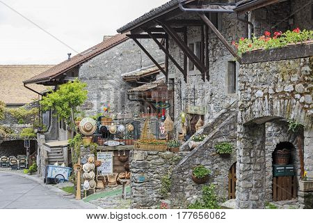 Yvoire France - May 24 2013: Townhouses which were built of stone can be seen along the street in medieval town. On a ground floor operate various stores and restaurants that are tourist attraction