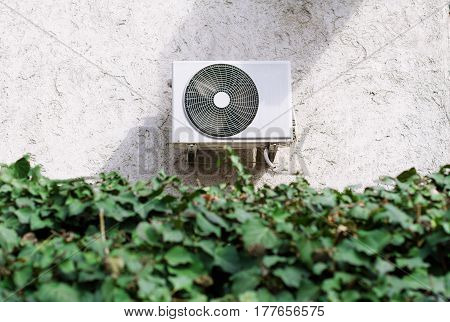 horizontal front view of a white air conditioning unit behind a decorative garden wall of green leaves