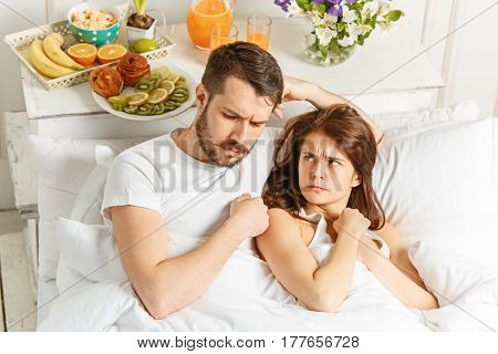 Relaxed Couple in Bed in bedroom at home at morning and colorful breakfast. The bad mood. Quarrel