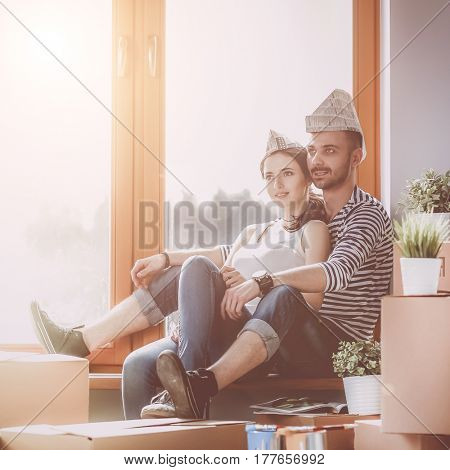 Couple moving in house sitting on the windowsill