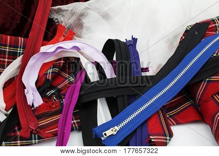 A pile of different zippers and fabric for sewing