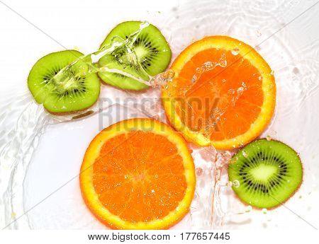 orange and kiwi in water white .