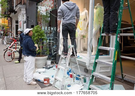 Workers Paint  The Front Of Ready-made Clothing Store