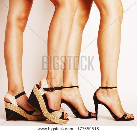 two pair of woman legs in hight heels shoes isolated on white