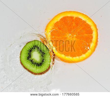 kiwi and orange in water on white background .