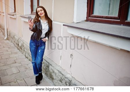 Portrait Of Stylish Young Girl Wear On Leather Jacket And Ripped Jeans With Mobile Phone At Hand Mak