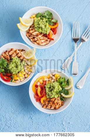 Grilled chicken fajitas bowls on a blue background top view. Flat lay