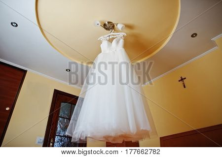 White Wedding Dress At Hangers On The Chandelier At Ceiling.