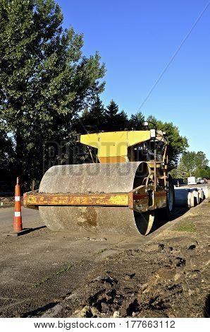 A heavy  industrial roller packs the top layer of sand prior to the applying of a new layer of asphalt on a street construction project
