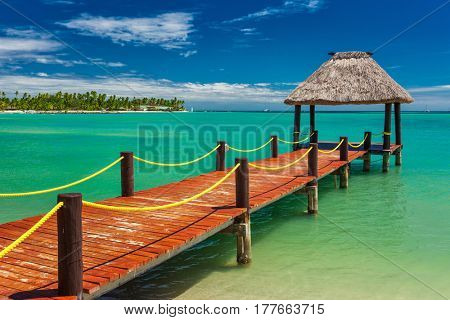 Wooden red jetty extending to tropical green lagoon, Fiji Islands
