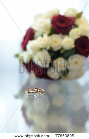 Gold wedding rings lie on a glass table next to the bouquet