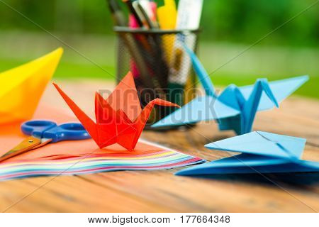 Closeup shot of a origami birds made with colorful paper on a wooden table