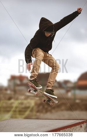Close up of a skateboarders feet while skating active performance of stunt teenager shot in the air on a skateboard