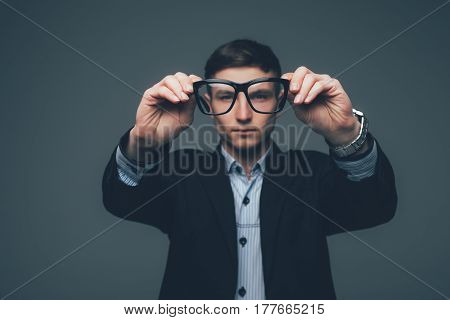 Business Man Is Looking Through The Glasses On Grey
