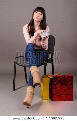 Cheerful young woman holding small gift box isolated over grey background and looking upward