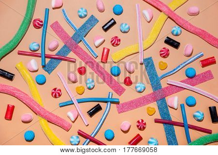Top view of a mixed multicolored sweet candies and lollies isolated on pink background