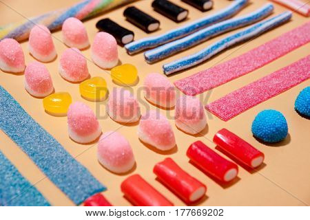 Close up of mixed multicolored sweet candies and lollies isolated on pink background