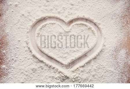 Love baking concept. Bakery class or recipe concept on white background, sprinkled wheat flour and heart symbol with copy space. Top view on wooden board or table. Cooking dough or pastry.