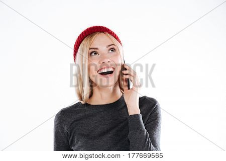 Close up portrait of a happy excited woman talking on mobile phone and laughing isolated over white background