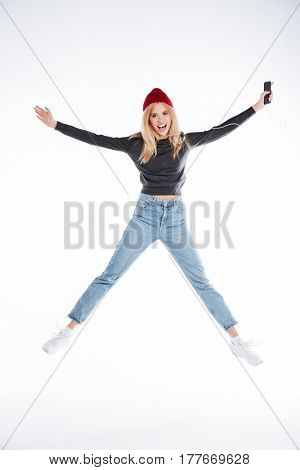 Full length portrait of a cheerful casual young woman listening music with earphones and jumping over white background over white background
