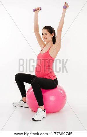 Full length portrait of a young pregnant woman doing exercise using fitness ball and dumbbells isolated over white